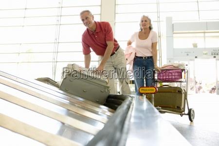aelterer mann koffer aus gepaeck karussell