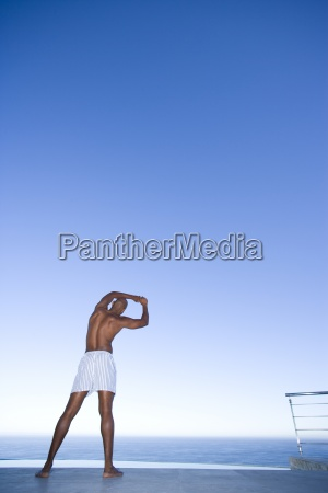 young man stretching arms by sea