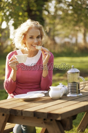 a mature woman having coffee and