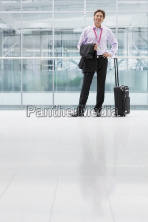 portrait of smiling businessman with suitcase