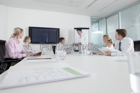 engineer in lab coat leading meeting