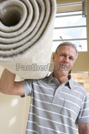 aelterer mann mit zusammengerollten teppich auf