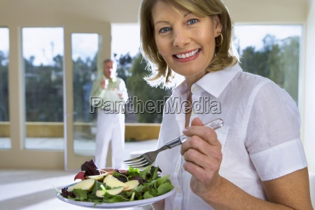 mature woman eating salad on plate