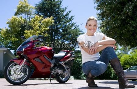 woman crouching near red motorbike on
