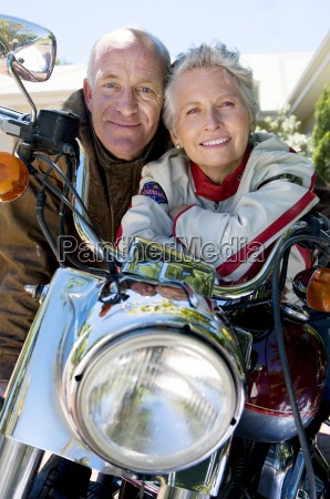 senior couple sitting on motorbike on