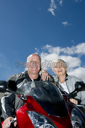 senior couple posing beside red motorbike