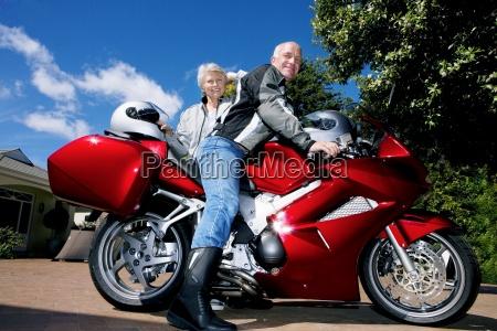 aelteres paar posiert neben rotem motorrad