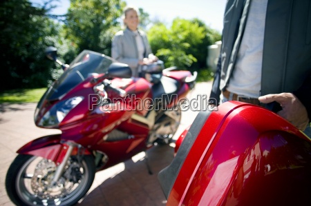 woman standing beside red motorbike on