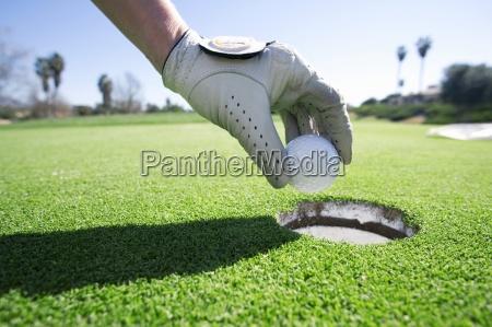 person die golfball aus dem loch