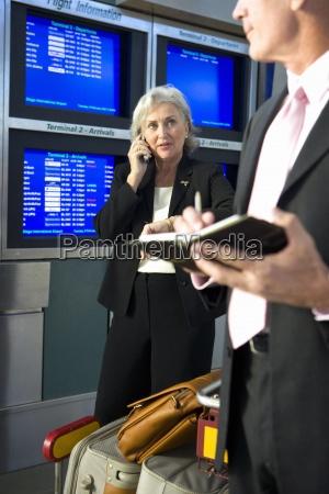 business paar neben reihe von fluginformationen