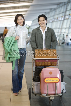 couple pushing luggage trolley in airport