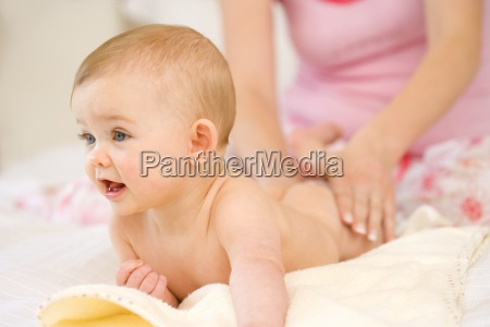 mother massaging baby girls 9 12