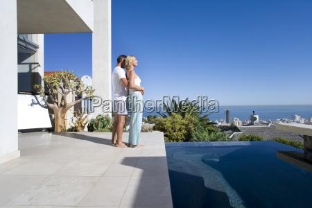 paar auf dem balkon durch swimmingpool