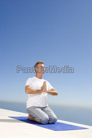 aeltere menschen meditieren auf gymnastikmatte im