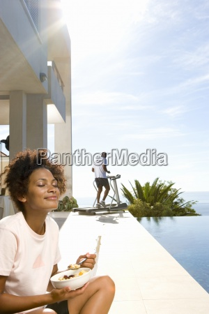 woman sitting outdoors with bowl of