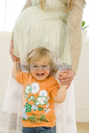 pregnant woman holding hands of toddler