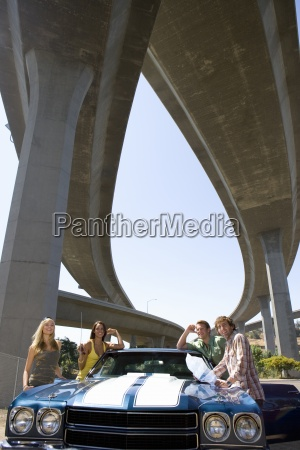 two young couples by car beneath