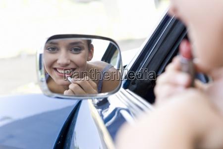 junge frau die lippenstift im rueckspiegel