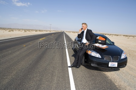 businessman using mobile phone by car