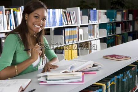 young woman studying in library smiling