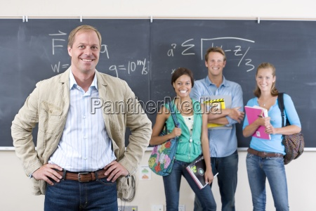 teacher and students by blackboard in