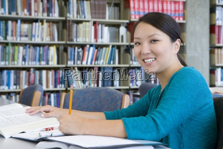 young woman studying in libaray smiling