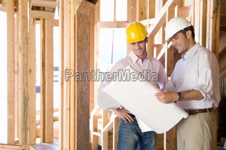 architect showing blueprint to man in