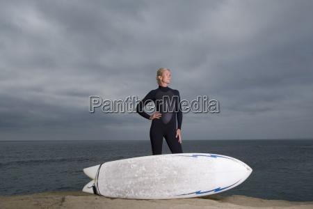 kobieta surfer w kombinezon z deska