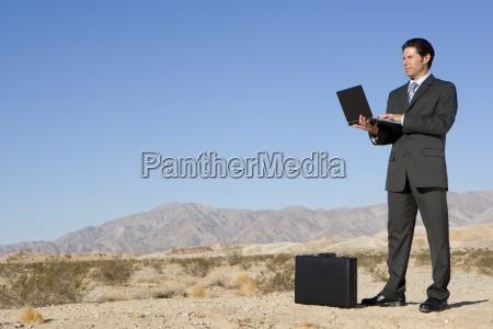geschaeftsmann mit aktenkoffer mit laptop computer