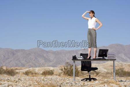 businesswoman stojacych na biurku w pustyni