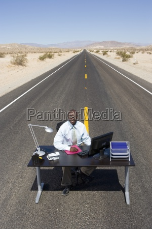 businessman at desk in middle of