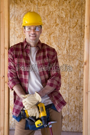 young man holding drill on construction
