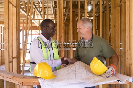 businessman and builder shaking hands by