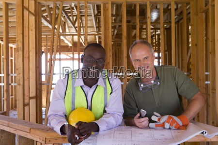 businessman and builder with blueprints in