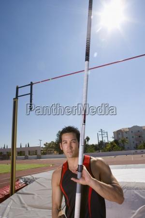 junge maennliche stabhochsprung athlet mit pole
