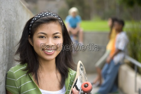 teenage girl 13 15 with skateboard