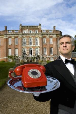 reife butler mit telefon auf tray