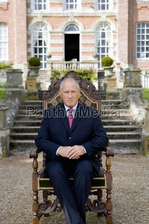 mature man on chair in grounds