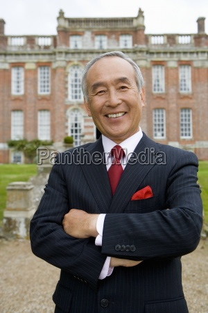 mature businessman with arms crossed in