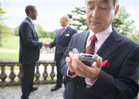 businessman using mobile phone by colleagues