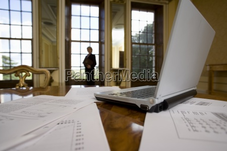 laptop computer and paperwork on table