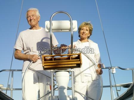 senior couple at wheel of boat