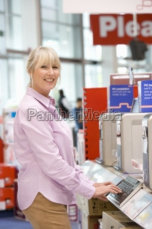 mature woman shopping for computer smiling