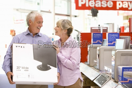 mature couple shopping man holding computer