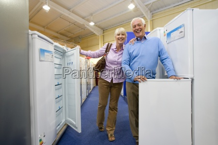 mature couple shopping for appliances smiling
