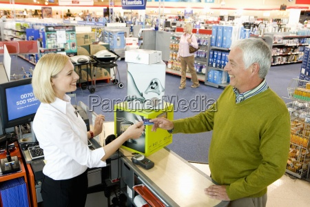 mature man paying cashier smiling elevated