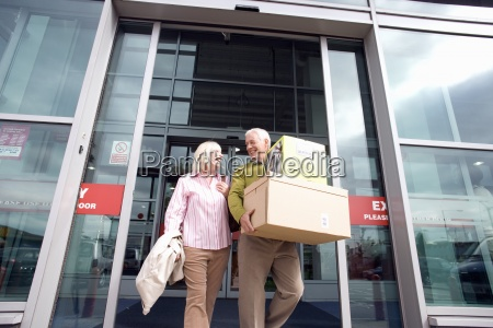 mature couple leaving shop with boxes