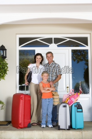 family of three with luggage by