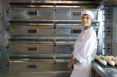 female baker by tray of baguettes