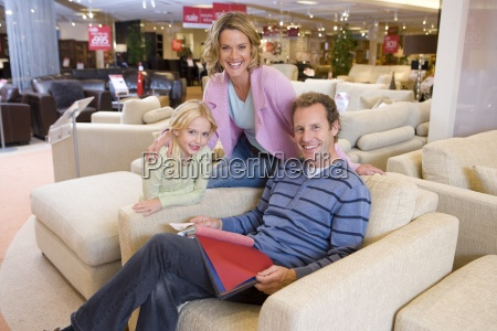 family of three in furniture shop